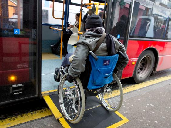 A man in a wheelchair boards a city bus via a ramp. (photo credit theasiantoday.com))